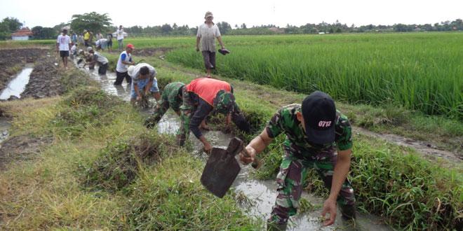 Anggota Koramil dan Masyarakat Bersihkan Saluran Irigasi