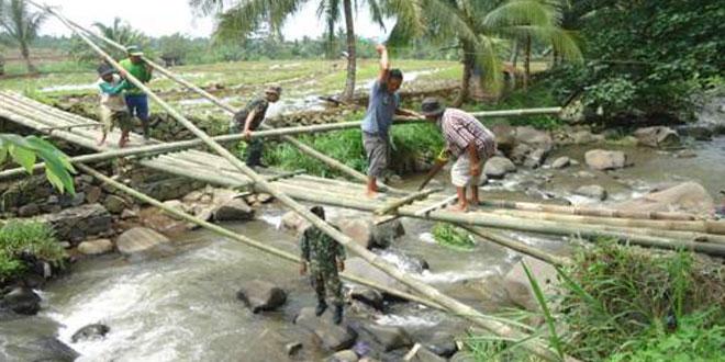 Anggota Koramil 15/Pekuncen Bersama Warga Membangun Jembatan