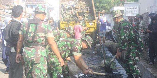 Anggota TNI Bersama Masyarakat Bersihkan Pasar