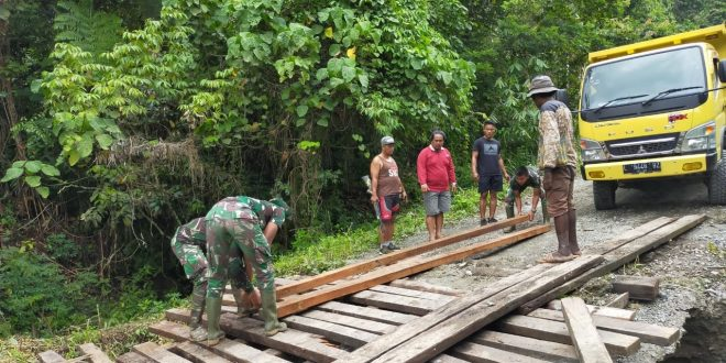 Akibat Jalan Longsor, TNI Melalui Satgas Pamtas Yonif 403/WP Bersama Masyarakat Sekitar Membangun Jembatan di Jalur Trans Papua
