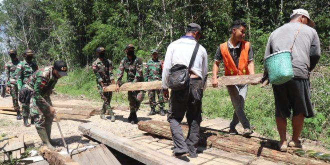 Tingkatkan Kenyamanan Fasilitas Umum, Satgas Yonif 407/PK Bersama Warga Perbaiki Jembatan